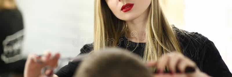 剪在理发店沙龙的理发师妇女男性头发 免版税库存图片