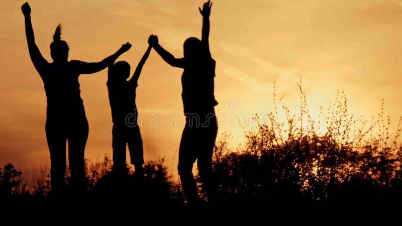 剪影、愉快的孩子有母亲的和父亲,家庭在日落 免版税图库摄影