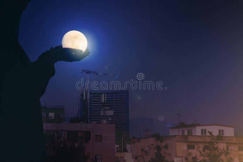 剪影与满月的妇女画象在城市夜光bokeh背景中 库存照片