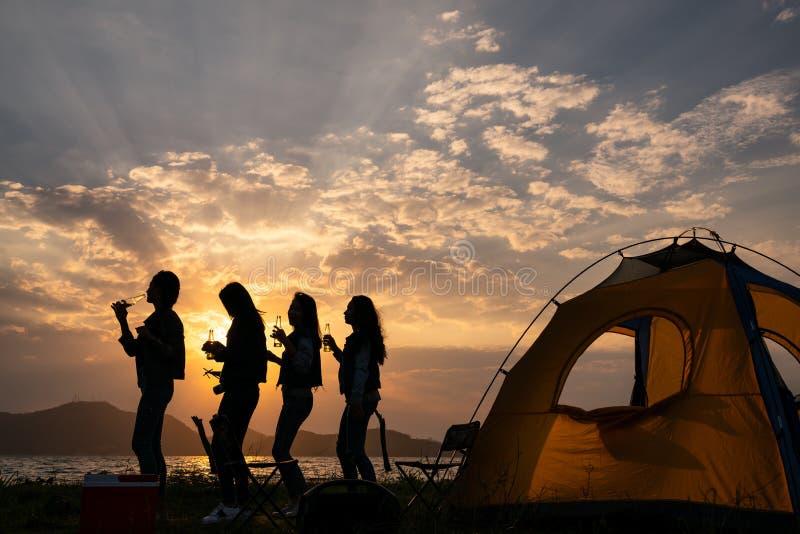 剪影与饮料瓶的小组少年亚洲女孩跳舞和党愉快享受旅行野营在湖旁边的在日落 免版税库存图片