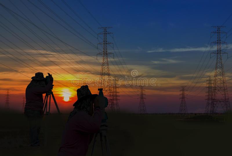 剪影人在电塔杆constructio的工作调查 库存照片