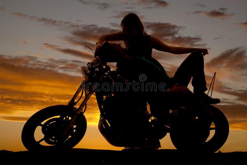剪影人在他的摩托车妇女向后倾斜 免版税库存图片