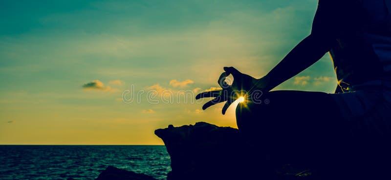 剪影在山日落的女子瑜伽 新工作日开始 图库摄影