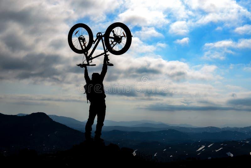 剪影在山顶的自行车骑士成功 免版税库存图片