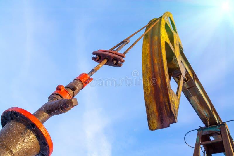 剪影在日落天空背景的油泵 石油工业设备 关闭工业看法在油 免版税库存照片