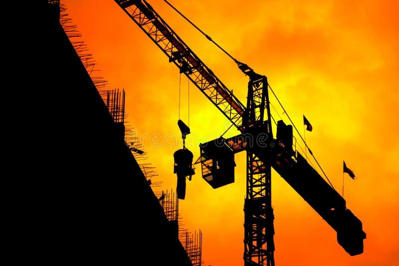 剪影塔吊在日落日出时间背景的建筑工作和拷贝空间增加文本 免版税库存图片