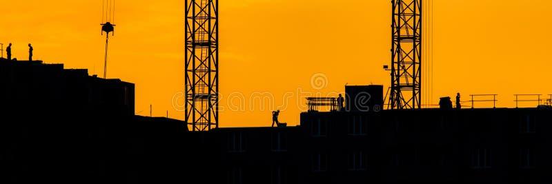 剪影大厦起重机背景举与太阳落山光芒黄色多云平衡的天空背景工地工作的装载在 图库摄影