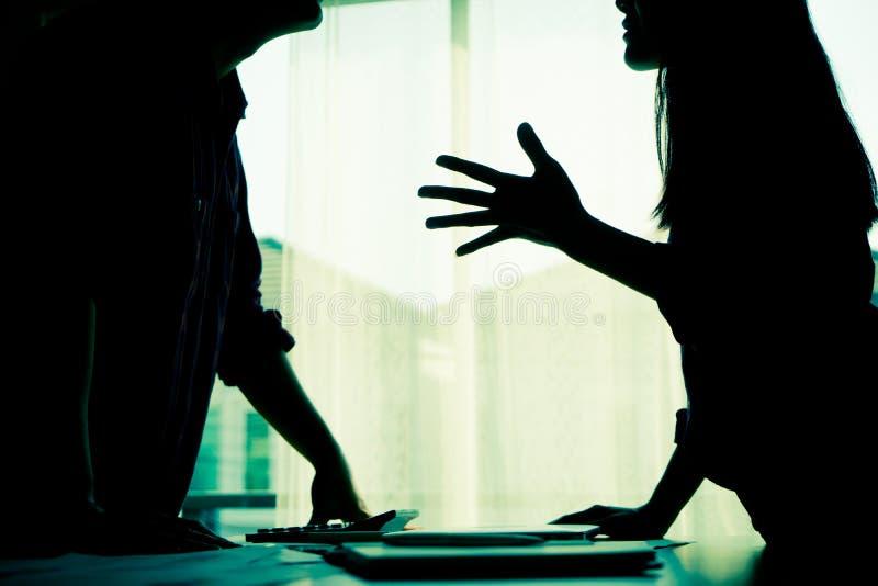 剪影夫妇由窗口战斗 免版税库存照片