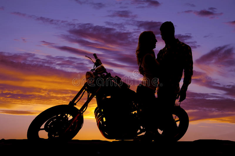 剪影夫妇看看彼此在摩托车 图库摄影