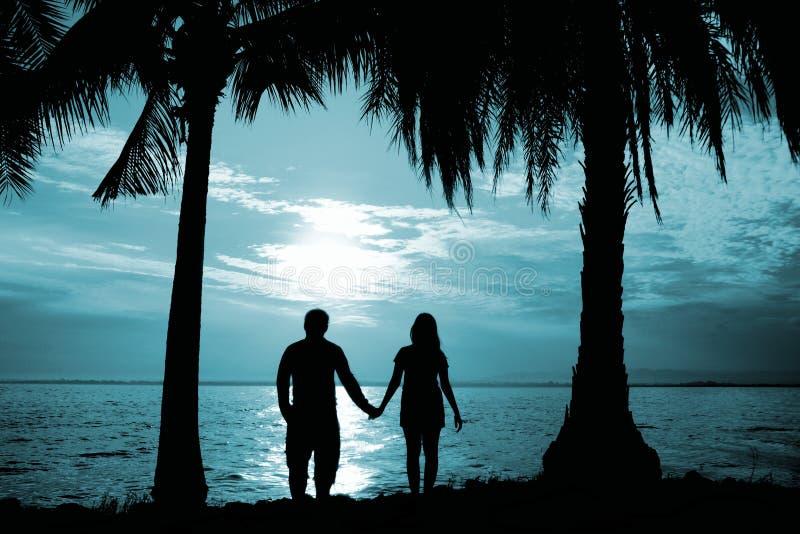 剪影夫妇站立在海前面的举行手 免版税图库摄影
