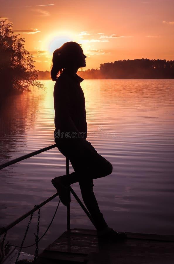 剪影女孩背景太阳 站立近的水的女孩户外 金子日落湖 考虑某事河du的少妇 免版税库存照片