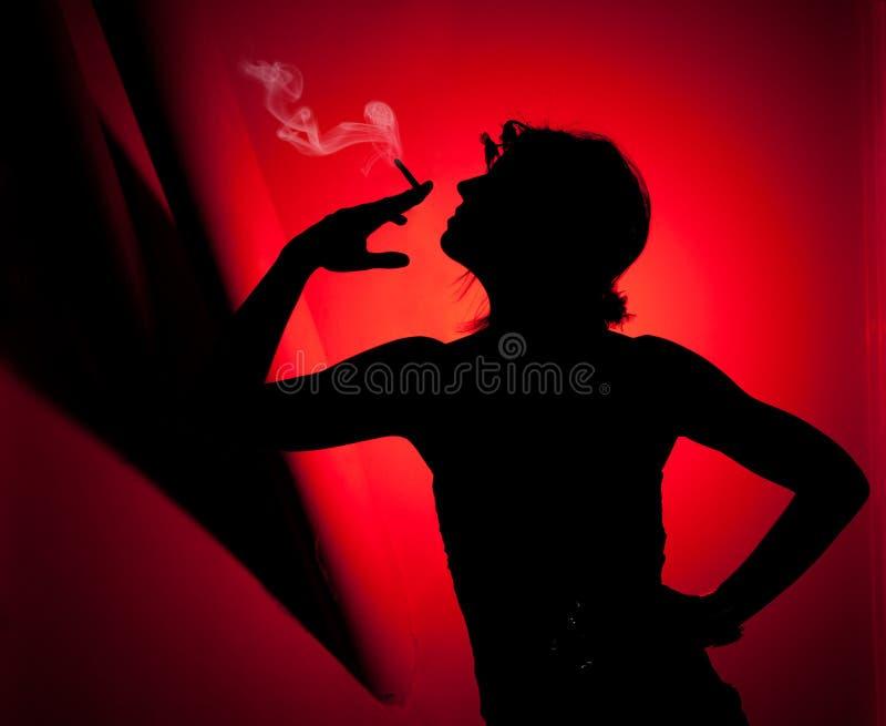 剪影妇女抽烟 免版税库存照片