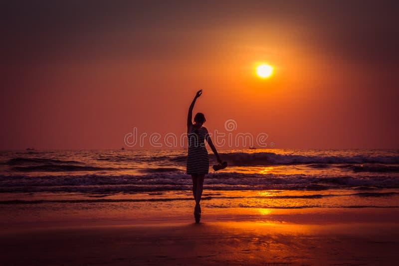剪影妇女的惊人的日落画象Arambol海滩的 库存图片