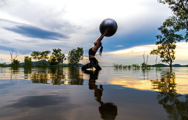 剪影少妇生活方式行使重要思考,并且实践反射在水洪水在水库, backgr的树 免版税库存照片