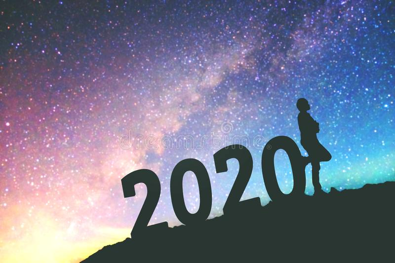 剪影年轻人愉快为2020在银河星系的新年背景 库存照片