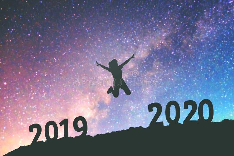 剪影年轻女人愉快为2020在银河星系的新年背景 库存照片
