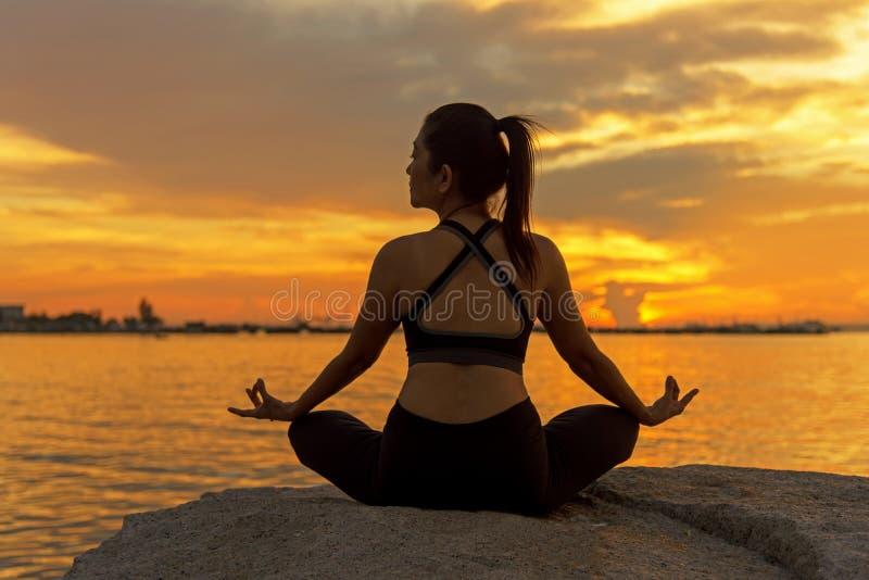 剪影年轻女人生活方式行使重要在海滩思考和实践的瑜伽球在日落 免版税库存图片