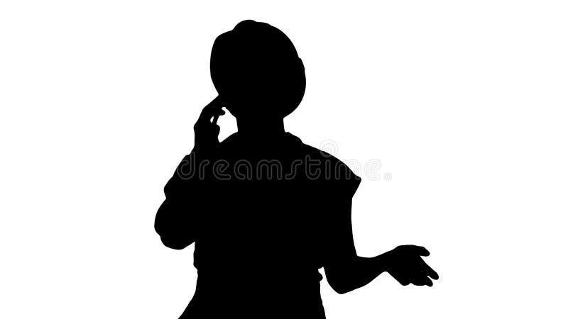 剪影年轻女工谈话在电话,当走时 免版税图库摄影