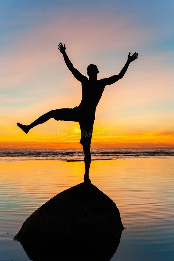 剪影快乐平衡在水滑稽的人的石头 图库摄影