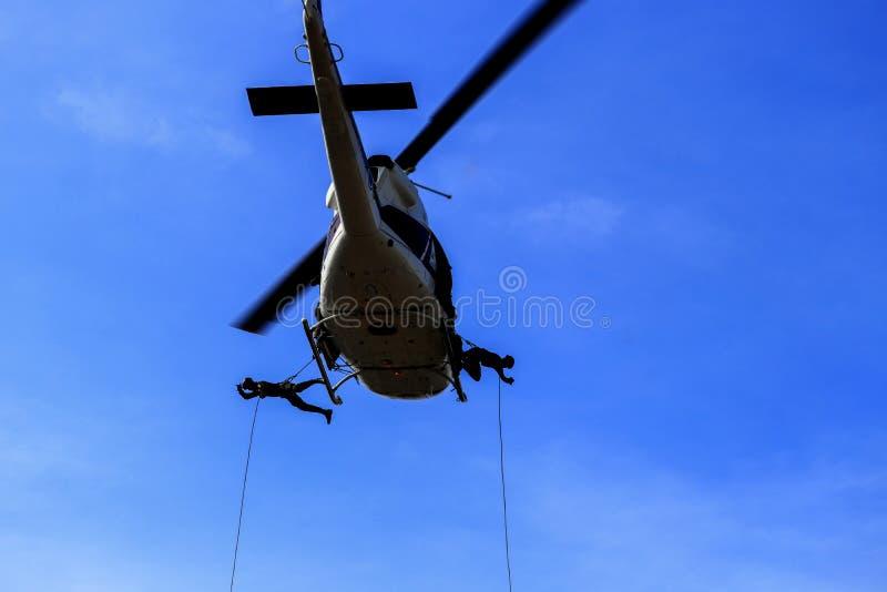 剪影战士从直升机的跳绳在蓝天 库存图片