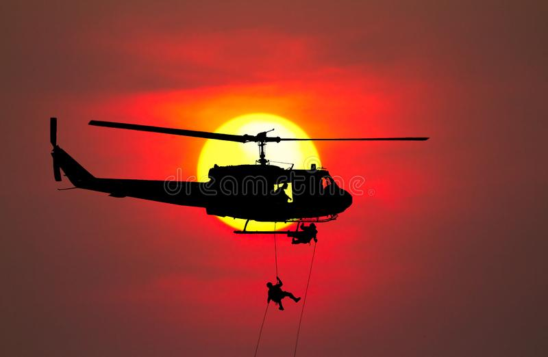 剪影战士坐式下降法下来从有战士的直升机攻击当心在地面日落背景迷离的危险 免版税图库摄影