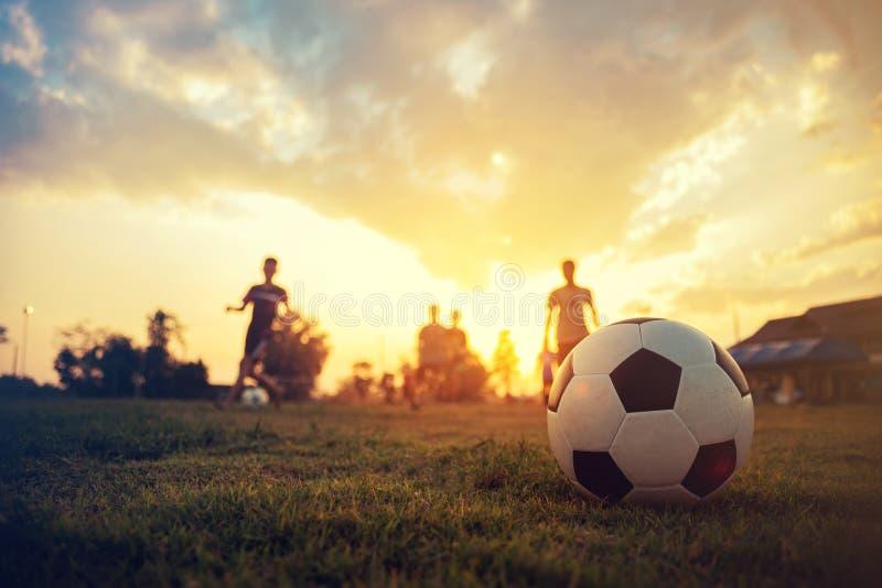 剪影户外行动体育一个小组孩子获得踢锻炼的乐趣足球橄榄球在社区农村下 库存图片