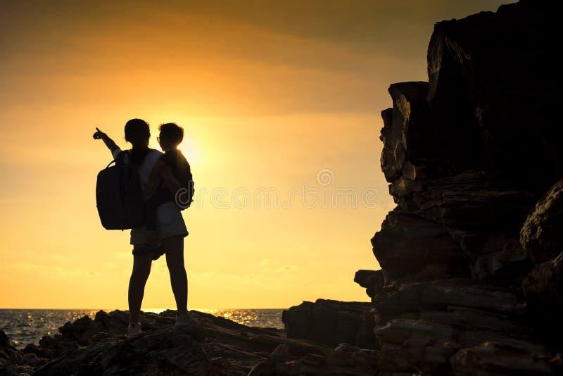 剪影母亲和儿子海上享受日落 图库摄影