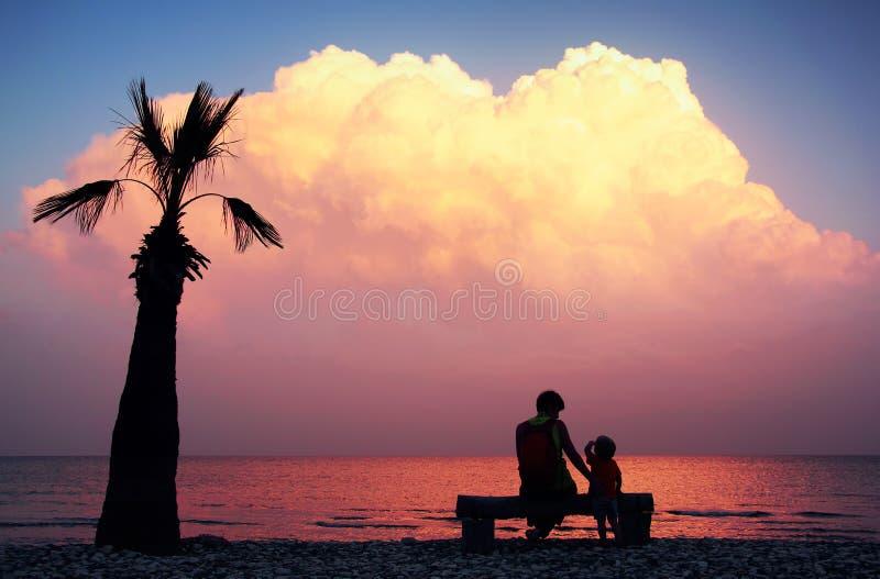 剪影母亲和她的小孩儿子坐在一个空的海滩的长凳与偏僻的棕榈树并且看惊人的紫色日落 免版税图库摄影
