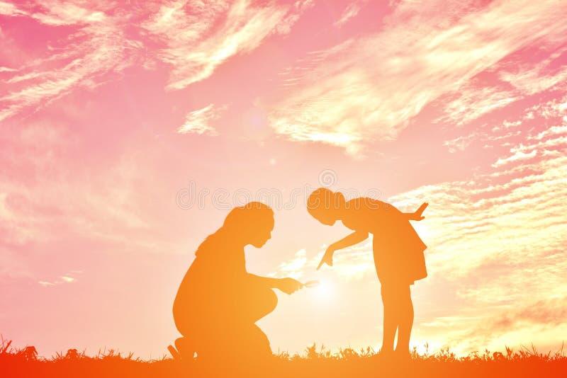 剪影照顾和女儿使用 免版税库存图片