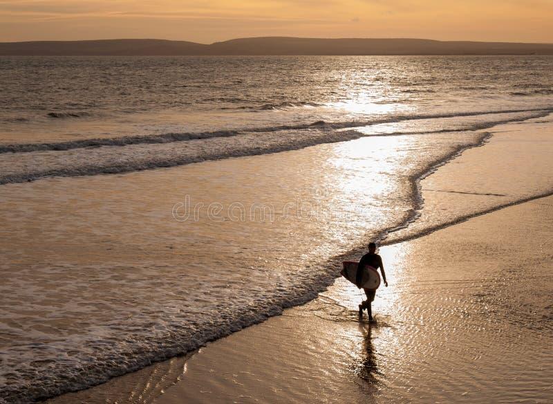 剪影的冲浪者从海走出去的 免版税库存图片