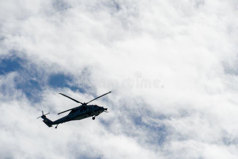 剪影盘旋在美好的天空背景的军队直升机 库存照片