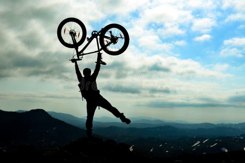 剪影自行车骑士在山顶庆祝 库存照片