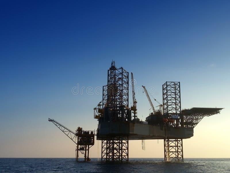 剪影近海抽油装置钻井平台 免版税库存照片