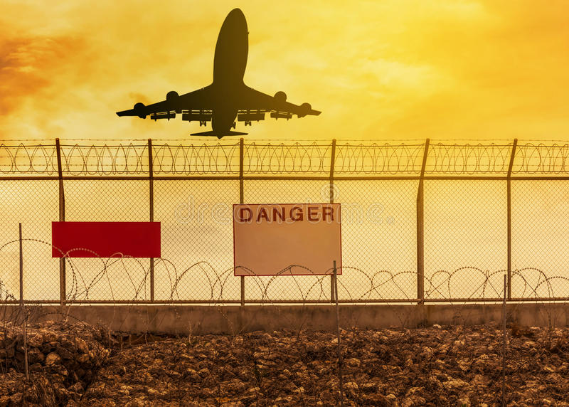 剪影飞机飞行从跑道离开有安全剃刀铁丝网金属篱芭背景 免版税库存照片
