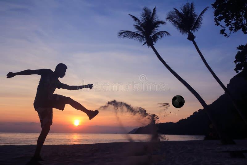 剪影齐射在海滩的反撞力橄榄球,在日出的亚洲人戏剧足球 免版税库存照片