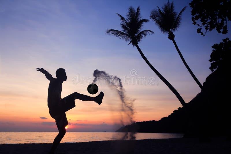 剪影齐射在海滩的反撞力橄榄球 库存图片