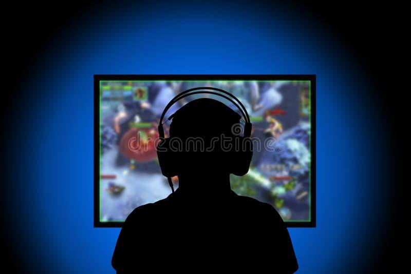 剪影,在家打在个人计算机的年轻人电子游戏 图库摄影