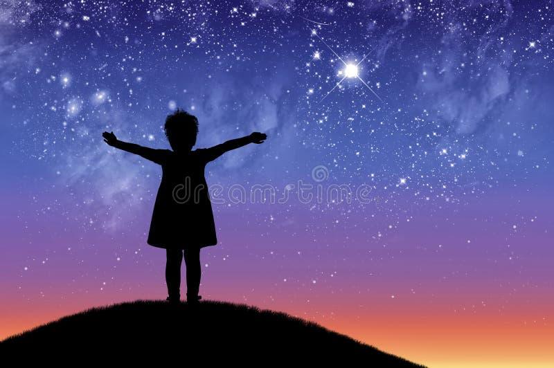 剪影,站立在小山的小愉快的女孩孩子看不满天星斗的美丽的天空 免版税库存图片