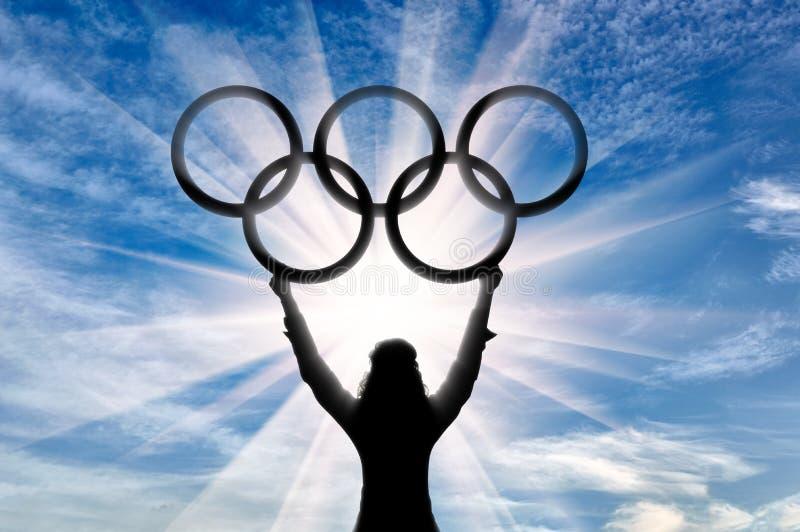 剪影?lympic运动员举了他的手并且拿着奥林匹克圆环 向量例证