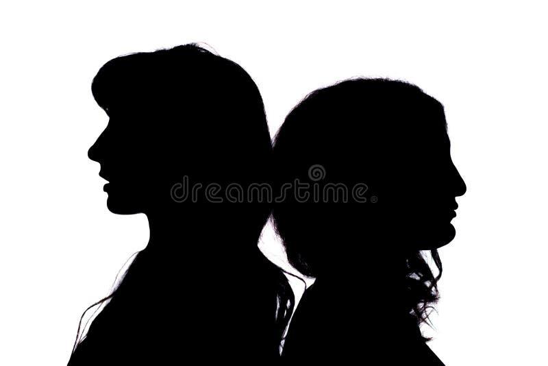 剪影 两个女孩互相站立与他们的后面在白色背景 免版税图库摄影