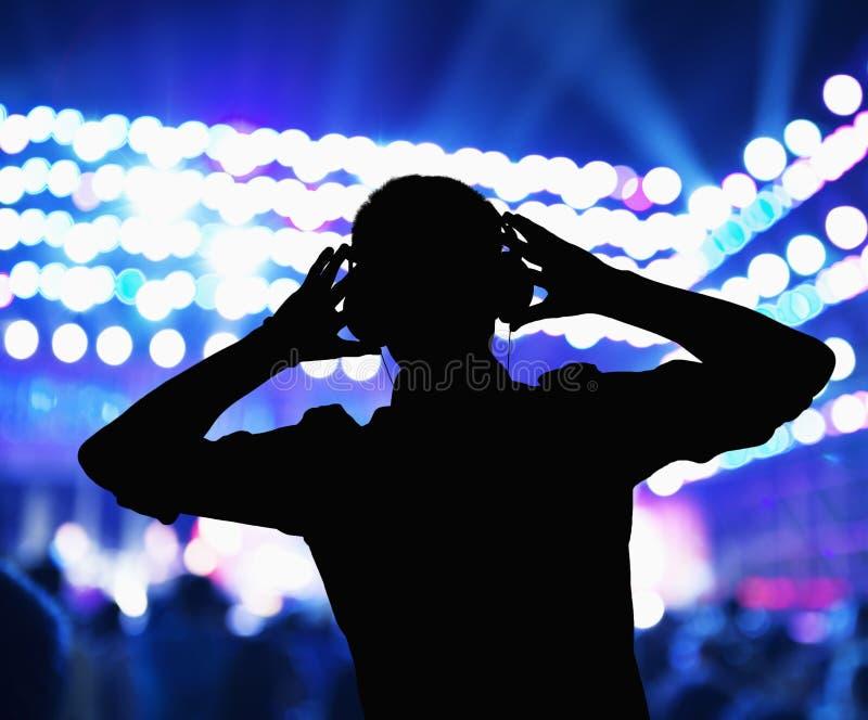 剪影DJ佩带的耳机和执行在夜总会 库存照片
