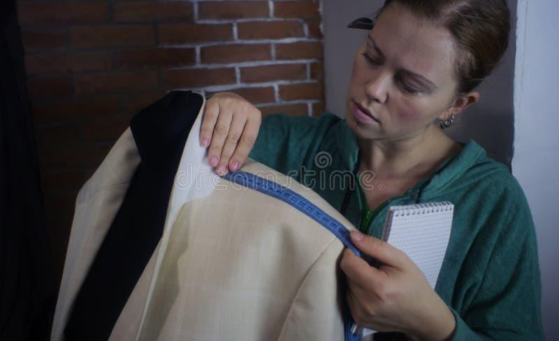 剪裁的工艺车间 修理人的轻的夹克的年轻裁缝,测量在时装模特的维度 定调子, 免版税图库摄影