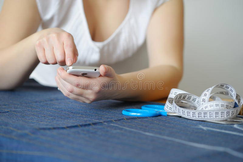 剪裁自然羊毛 使用智能手机的妇女裁缝 图库摄影