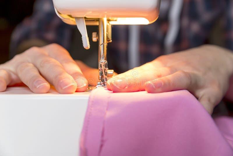 剪裁过程-妇女在她的缝纫机后的` s手 库存图片