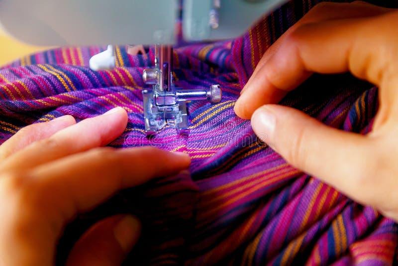 剪裁过程-妇女在她缝合后的` s手 紫色织品 免版税库存图片