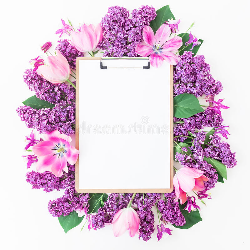 剪贴板、郁金香和淡紫色分支在桃红色背景 平的位置,顶视图 秀丽博克概念 免版税库存图片