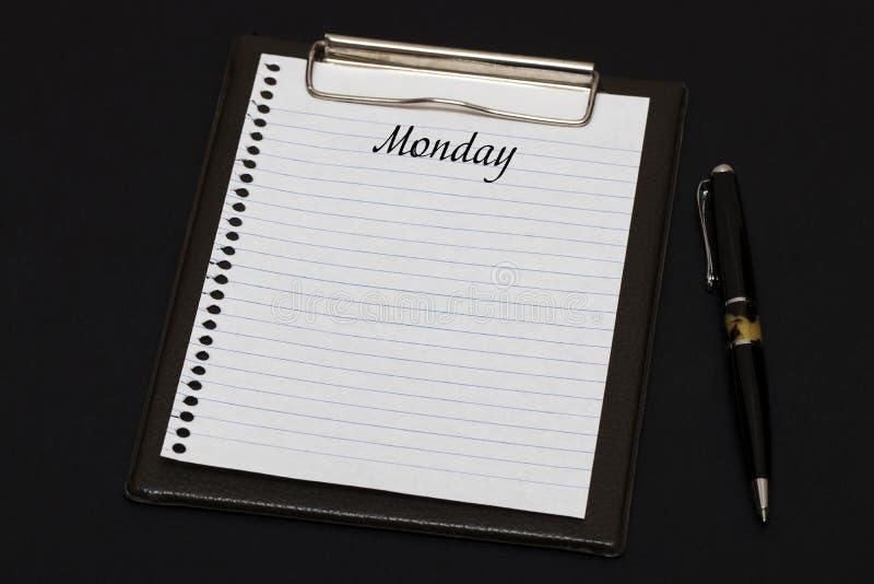 剪贴板和白色板料顶视图写与星期一在bla 库存照片
