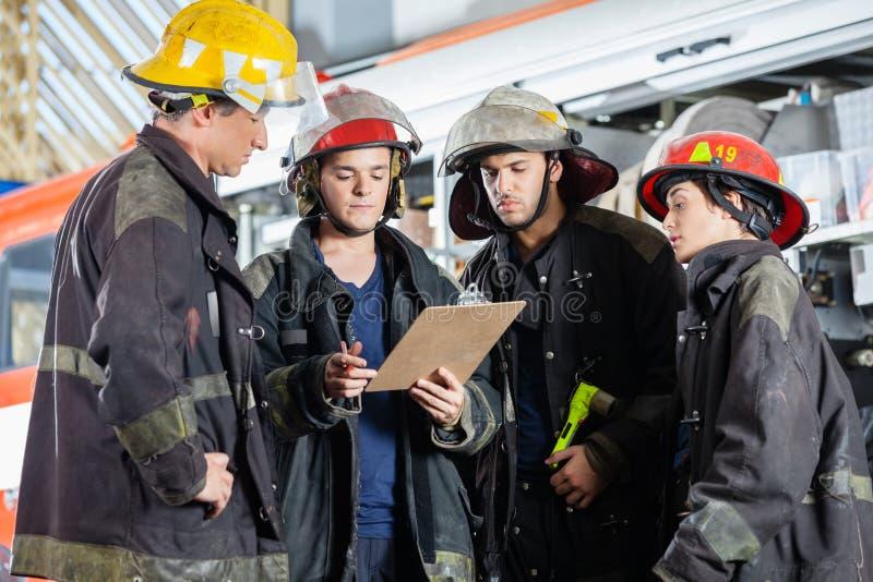 读剪贴板的消防队员在消防局 免版税库存照片