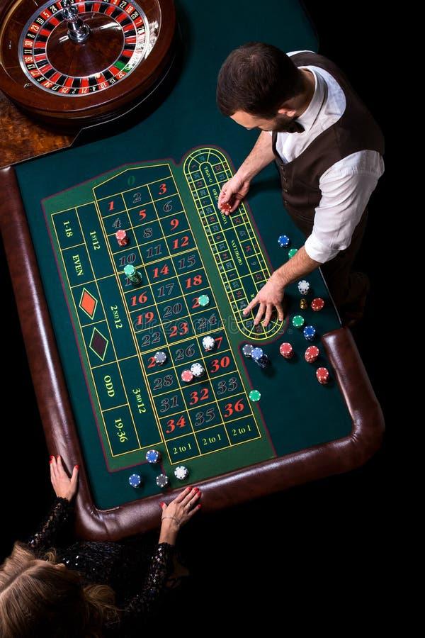 副主持人和妇女球员在一张桌上在赌博娱乐场 a.c.的图片 免版税库存照片
