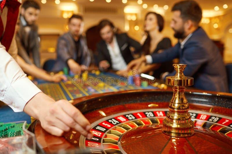 副主持人在一个赌博娱乐场在他的手上拿着一个轮盘赌用球 免版税库存照片